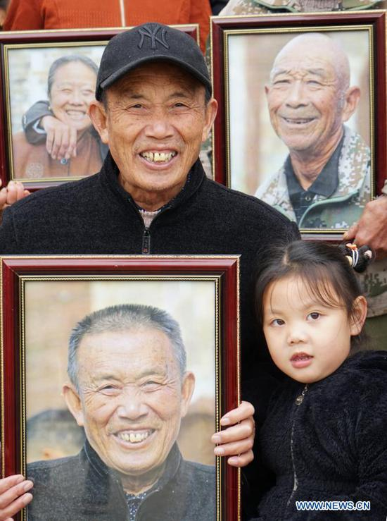 A villager smiles as he holds his photo in Luoshe Village of Youlan Town, Nanchang City, east China's Jiangxi Province, Nov. 22, 2020. Since 2014, volunteers from a non-profit organization in Nanchang City have kept on taking photos of smiling faces of farmers aged over 70 years old in nearby villages. The portait photos taken by volunteers were given to farmers for free. By far, the volunteers have taken nearly 4,350 people and 50,000 photos. They aim at collecting high-definition images of 10,000 farmers within 10 years. (Xinhua/Chen Chunyuan)