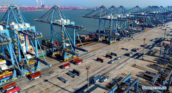 Aerial photo taken on Feb. 19, 2021 shows containers at the automatic dock of the Qingdao port in Qingdao, east China's Shandong Province. During this year's Spring Festival holiday, the Qingdao port has handled 12.47 million tonnes of cargo, up 12.8 percent year on year. (Photo by Zhang Jingang/Xinhua)