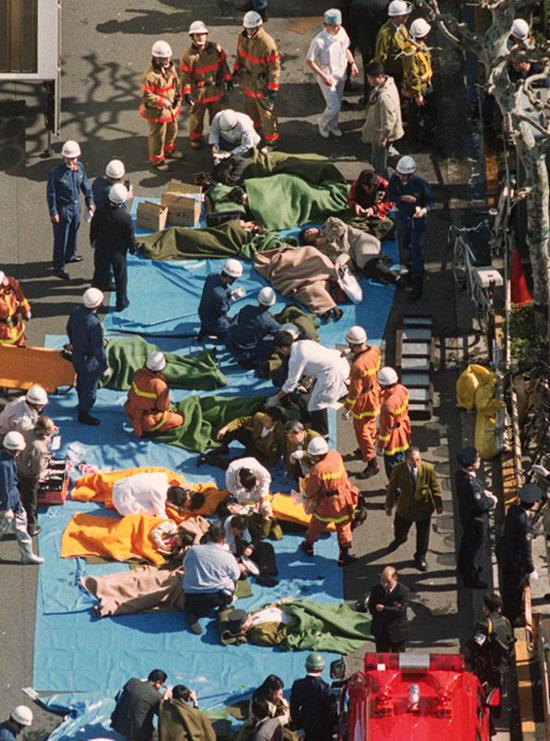 In this March 20, 1995, file photo, the injured of the deadly gas attack are treated by rescuers near Tsukiji subway station in Tokyo. Japanese media reports say on Friday, July 6, 2018, doomsday cult leader Shoko Asahara, who has been on death row for masterminding the 1995 deadly Tokyo subway gassing and other crimes, has been executed. He was 63. (Kyodo News via AP, File)