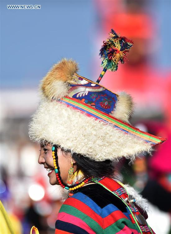 A woman wearing a hat is seen during a horse racing festival in Nagqu City, southwest China's Tibet Autonomous Region, Aug. 10, 2019. People in Amdo County of Nagqu City have a tradition of wearing hats, which are now mostly made from lamb skins and artificial leather.The hat usually has an antenna-like stripe of fabric at the top. (Xinhua/Chogo)