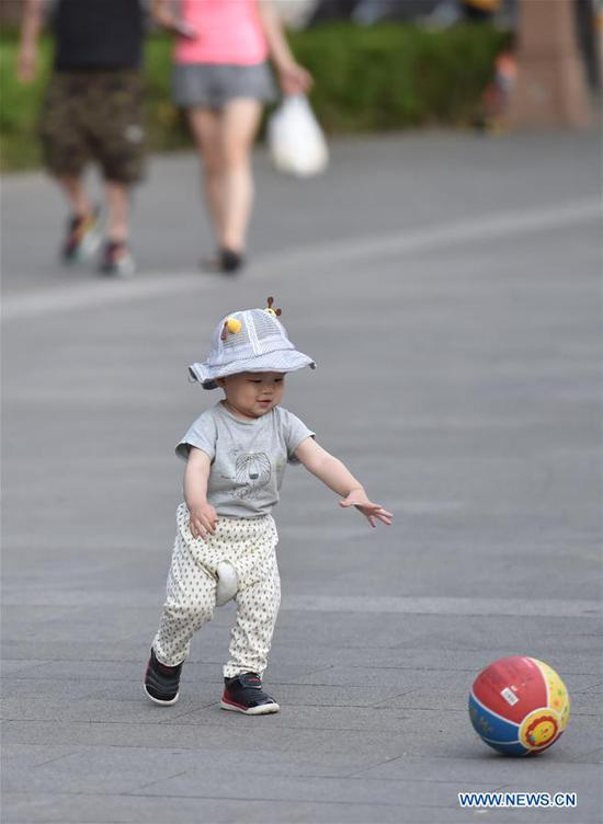 A kid plays a ball at the cultural square of the Bell and Drum Tower in Beijing, capital of China, May 31, 2020. (Xinhua/Chen Zhonghao)