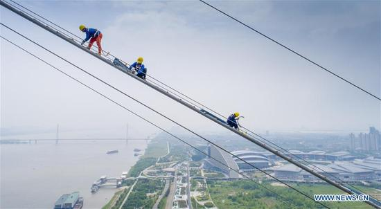 Workers install wire netting upon catwalk for construction of a bridge crossing the Yangtze River in Wuhan, capital of central China's Hubei Province, May 8, 2018. The 4.13-km double-deck road suspension bridge was built across China's longest river, the Yangtze. (Xinhua/Ke Hao)