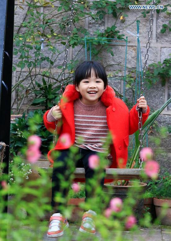 A child plays on a swing in Changtai County of Zhangzhou, southeast China's Fujian Province, Feb. 8, 2019. (Xinhua/Xiao Heyong)