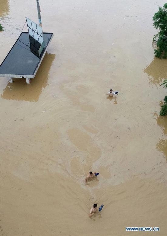 People wade through a waterlogged road at Banlan Township in Rongan County, Liuzhou City, south China's Guangxi Zhuang Autonomous Region, June 9, 2019. Guangxi's meteorological bureau on Sunday evening upgraded the meteorological disaster emergency response to level-II after rainstorms starting Tuesday caused flooding in several cities. (Xinhua/Tan Kaixing)