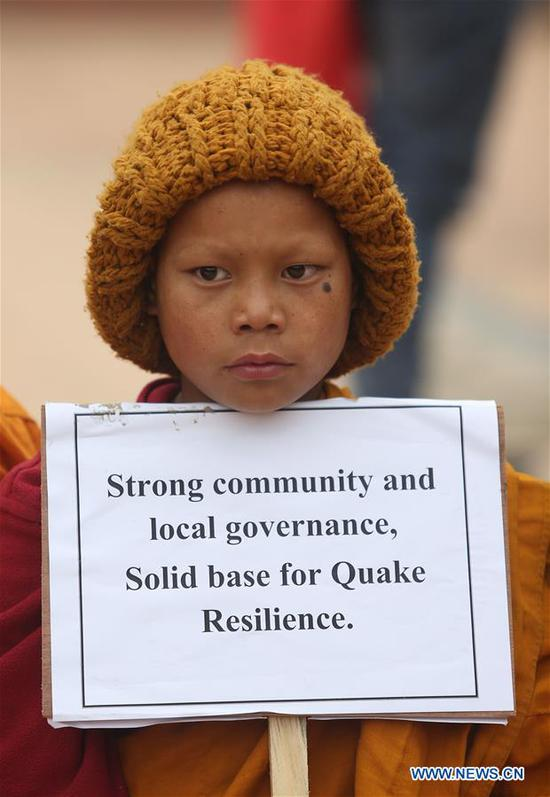 A monk holds a placard during an event marking Nepal's 22nd Earthquake Safety Day at Bhaktapur Durbar Square in Bhaktapur, Nepal, Jan. 16, 2020. Nepal marked the 22nd Earthquake Safety Day on Thursday, in commemoration of the devastation caused by 1934 Nepal-Bihar earthquake. Nepal faced another earthquake on April 2015, also known as the Gorkha earthquake,which killed nearly 9,000 people and injured more than 22,000. (Photo by Sunil Sharma/Xinhua)