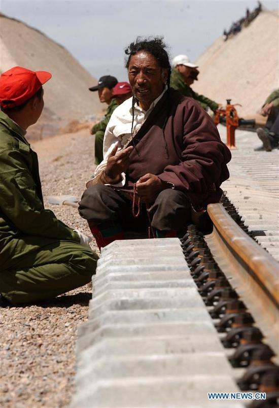 An ethnic Tibetan talks with a staff worker of the Qinghai-Tibet Railway on June 20, 2004. (Xinhua/Chogo)