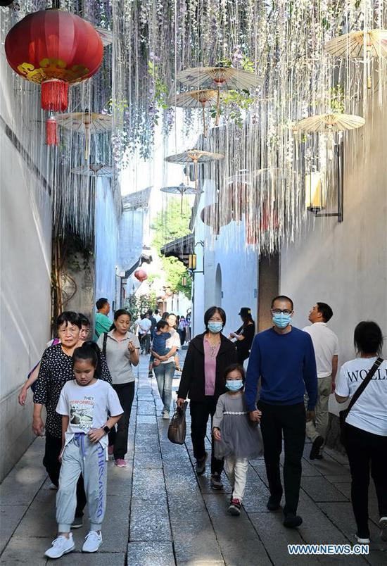 Tourists visit Sanfangqixiang (Three Lanes and Seven Alleys), a scenic spot in Fuzhou, southeast China's Fujian Province, Oct. 8, 2020. According to Fujian Provincial Department of Culture and Tourism, Fujian received over 39.3 million person-times of tourists during the eight-day National Day and Mid-Autumn Festival holiday ending on Thursday, marking a year-on-year increase of 5.5 percent. The province's tourism industry has raked in 34.09 billion yuan (about 5 billion U.S. dollars) in revenue during the holiday, up 10.2 percent from a year earlier. (Xinhua/Lin Shanchuan)
