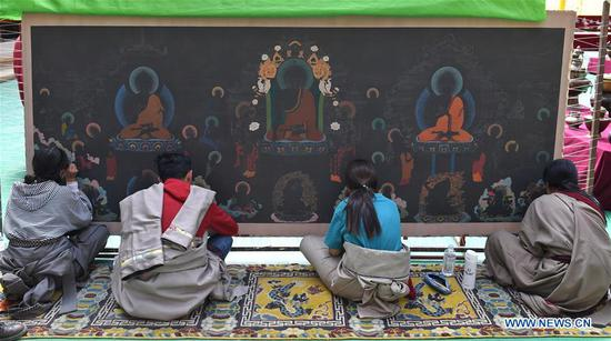 Students create a Tangka painting at a workshop where villagers can learn traditional crafts for free in Rangtang County of Aba Tibetan and Qiang Autonomous Prefecture, southwest China's Sichuan Province, June 13, 2020. Located in northwest of Sichuan Province, with nearly one million population, Aba Tibetan and Qiang Autonomous Prefecture has a diversity of ethnic minority groups, including Tibetan, Qiang and Hui, etc. In recent years, to better inherit the ethnic culture, local schools have introduced more traditional cultural courses while local authorities set up training workshops about intangible cultural heritage to help local villagers learn traditional crafts, as a way to boost their incomes. In 2018, the production value of cultural industry in this prefecture has reached about 1.2 billion yuan (about 169.8 million U.S. dollars), accounting for 3.32 percent of gross domestic product (GDP) of this prefecture. (Xinhua/Liu Kun)