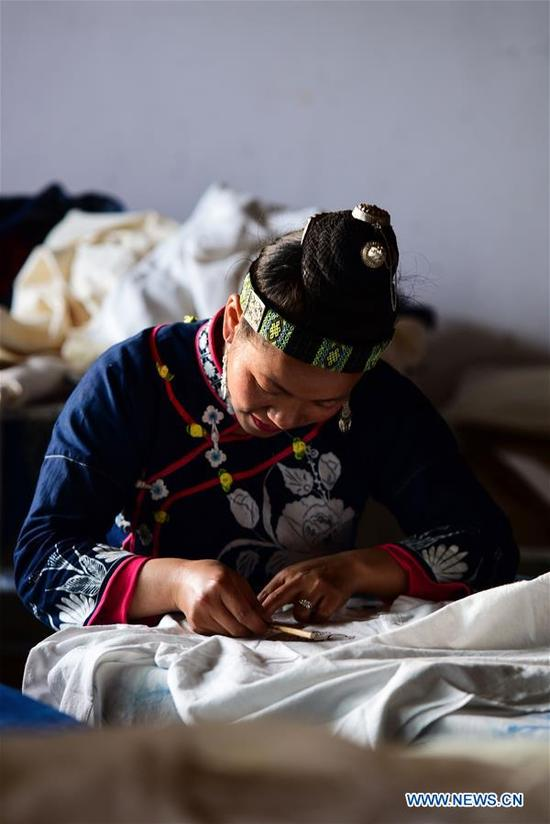 An artist makes batik at a cooperative in Danzhai County, southwest China's Guizhou Province, April 9, 2018. Relying on its intangible cultural heritage, Danzhai encourages local people to develop the business such as opening experience houses for visitors. This also becomes a means of helping local people get rid of poverty with this