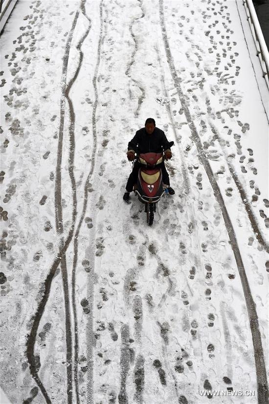 A man rides on a snow-covered road in Taiyuan, capital of north China's Shanxi Province, April 5, 2018. A cold front brought snowfall to parts of China in these days. (Xinhua/Zhan Yan)