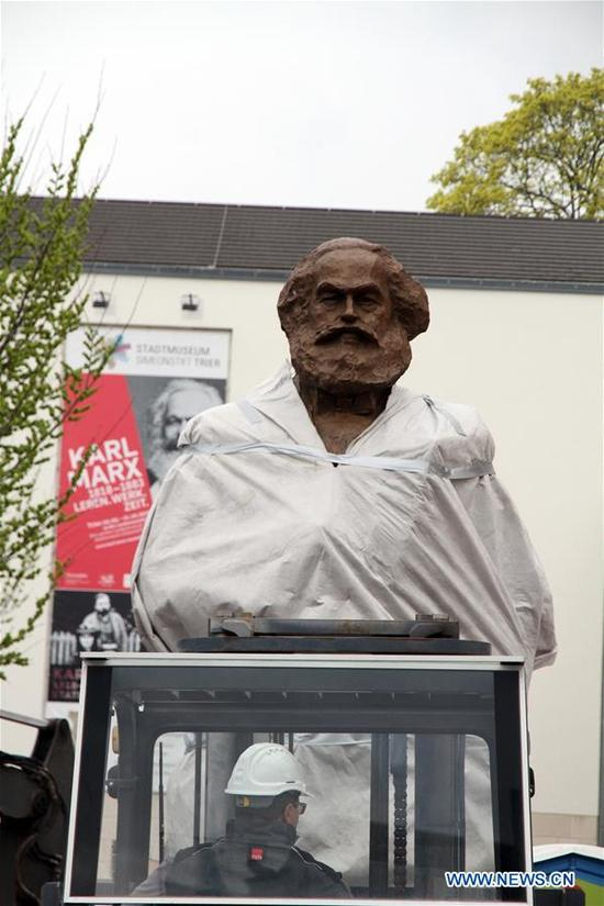 A worker drives forklift to move a Karl Marx statue towards the pedestal in Trier, Germany, April 13, 2018. A 4.4-meter monumental bronze statue of Karl Marx presented by China as a gift to the great thinker's hometown, was erected here Friday ahead of celebrations to mark the 200th anniversary since Marx's birth. (Xinhua/Shen Zhonghao)