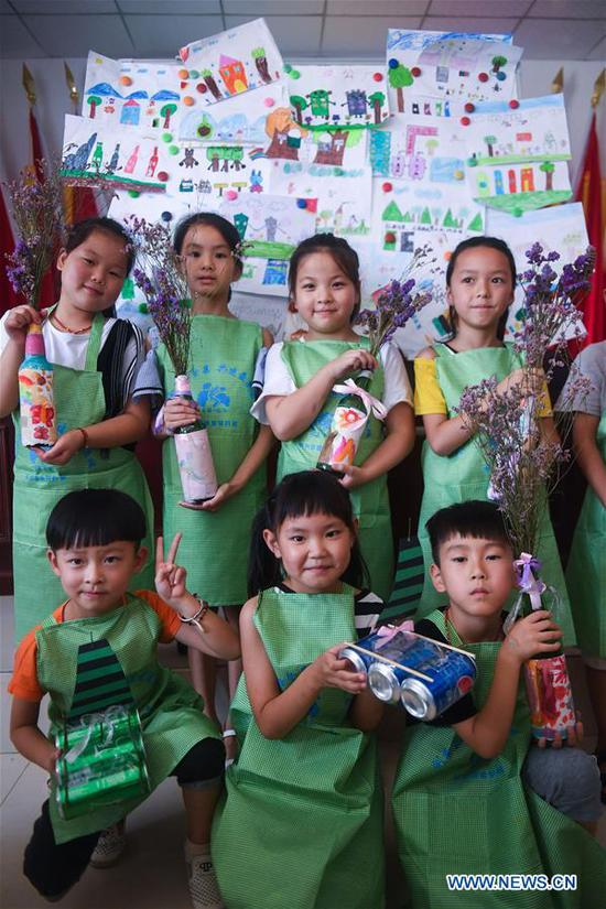 Students present the ornaments they made from waste materials during a class at a school in Lincheng Township in Changxing County, east China's Zhejiang Province, July 10, 2018. Volunteers from Hangzhou Normal University and government officials organized the class to teach students how to classify the garbage and reuse the waste. (Xinhua/Xu Yu)