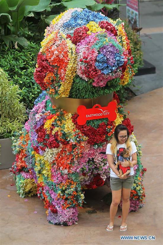 A woman holds her pet dog in front of a dog-shaped flower display during a pet parade in Quezon City, the Philippines, Oct. 7, 2018. (Xinhua/Rouelle Umali)