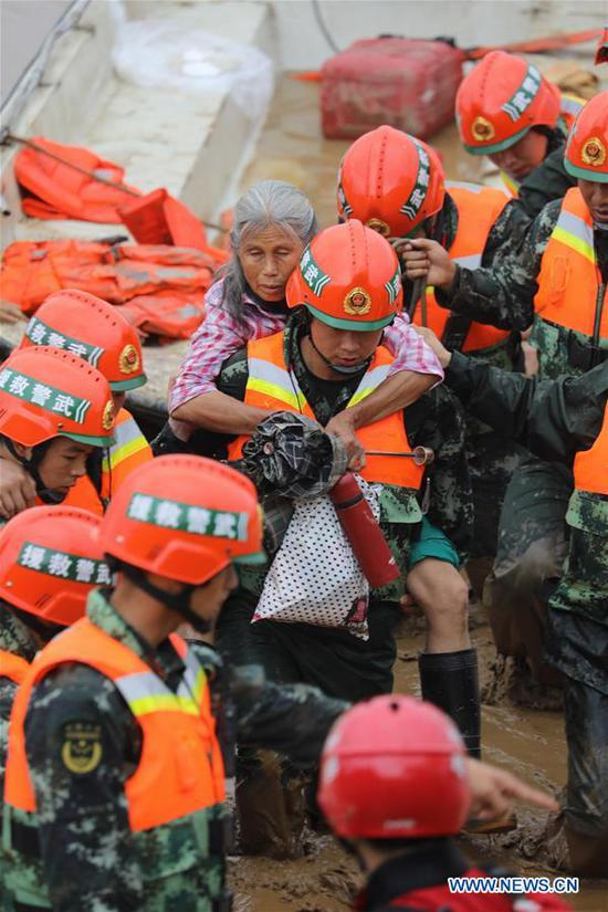 Rescuers transfer an aged woman at Zhaojia Village of Quanzhou County in Guilin, south China's Guangxi Zhuang Autonomous Region, June 9, 2019. Guangxi's meteorological bureau on Sunday evening upgraded the meteorological disaster emergency response to level-II after rainstorms starting Tuesday caused flooding in several cities. (Xinhua/Wang Zichuang)