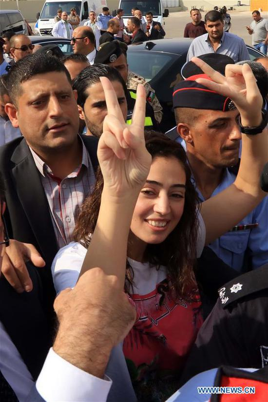 Released Jordanian Hiba Labadi flashes a victory sign on her arrival at the King Hussein Bridge border crossing, Jordan, Nov. 6, 2019. Jordanians Hiba Labadi and Abdulrahman Meri on Wednesday arrived in Jordan after their release from Israel, according to a statement by the Jordan's foreign ministry. The two Jordanians were detained by Israeli authorities after crossing the King Hussein Bridge on the Jordan-Israel border. (Photo by Mohammad Abu Ghosh/Xinhua)
