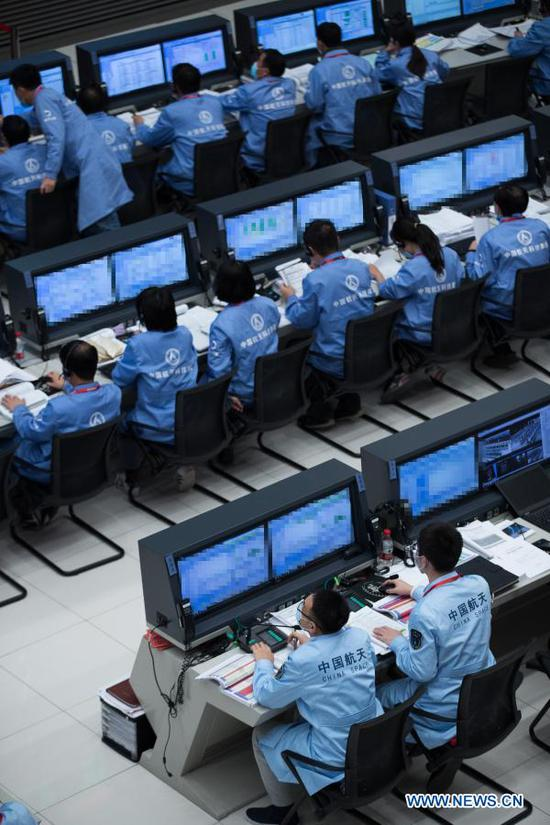 Technical personnel work at the Beijing Aerospace Control Center (BACC) in Beijing, capital of China, Dec. 1, 2020. China's Chang'e-5 spacecraft successfully landed on the near side of the moon late Tuesday and sent back images, the China National Space Administration (CNSA) announced. At 11:11 p.m., the spacecraft landed at the preselected landing area near 51.8 degrees west longitude and 43.1 degrees north latitude, said the CNSA. During the landing process, the cameras aboard the lander took images of the landing area, said the CNSA. (CNSA/Handout via Xinhua)