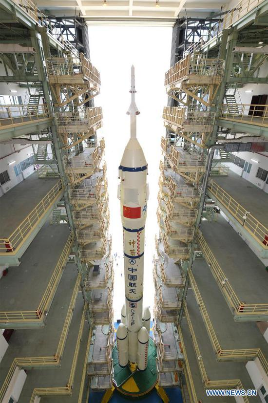 The combination of the Shenzhou-12 manned spaceship and a Long March-2F carrier rocket is being transferred to the launching area of Jiuquan Satellite Launch Center in northwest China, June 9, 2021. The combination of the Shenzhou-12 manned spaceship and a Long March-2F carrier rocket has been transferred to the launching area, the China Manned Space Agency (CMSA) said Wednesday. The facilities and equipment at the launch site are in good condition, and various pre-launch function checks and joint tests will be carried out as planned, said the CMSA. (Photo by Wang Jiangbo/Xinhua)