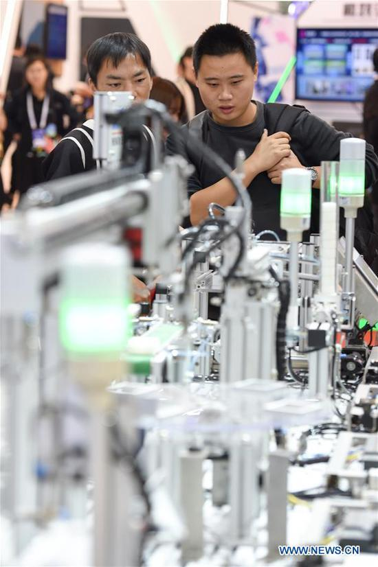 Visitors look at an automated modular production line during the World Intelligent Manufacturing Summit (WIMS) 2018 in Nanjing, east China's Jiangsu Province, Oct. 11, 2018. The WIMS 2018 opened at the Nanjing International Expo Center on Thursday. The event attracts over 1,900 exhibitors worldwide to showcase the latest technologies, advanced products, development trends and cutting-edge solutions in the intelligent manufacturing field. (Xinhua/Li Bo)
