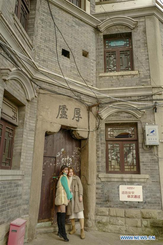 Visitors pose for photos in front of an old building along the 3rd footpath in Yuzhong district of Chongqing, southwest China, Dec. 2, 2018. Since 2016, local authority has rolled out plans to renovate 14 footpaths with a total length of 39.5 kilometers. The 14 footpaths linking Chongqing's natural and cultural highlights provide visitors the city's most beautiful and important sights. (Xinhua/Liu Chan)
