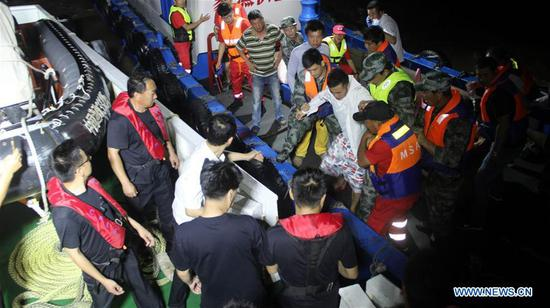 A man is rescued after a shipwreck accident in the waters northeast of Tantoushan Island in Xiangshan County of Ningbo City, east China's Zhejiang Province, July 11, 2018. Four people are still missing after their boat lost contact Tuesday night. Seven people have been rescued as of Wednesday evening. Typhoon Maria, the eighth this year, made landfall Wednesday morning in neighboring Fujian Province. (Xinhua/Xu Yongming)