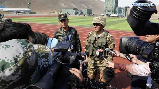 A soldier (R) from the National Guard of Kyrgyzstan receives an interview in Urumqi, northwest China's Xinjiang Uygur Autonomous Region, Aug. 6, 2019. The China-Kyrgyzstan