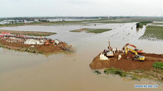 Rescuers block a dike breach on the Mihe River in Shouguang, east China's Shandong Province, Aug. 14, 2019. Rescuers are trying to repair dike breaches triggered by heavy floods brought by typhoon Lekima in Shouguang. (Xinhua/Wang Kai)