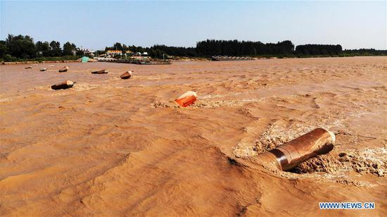 Pontoons are seen after the floating bridge over the Yellow River at Luokou is temporarily dismantled as a flood is expected to soon reach Jinan, capital of east China's Shandong Province, on Sept. 18, 2019. (Xinhua/Wang Kai)