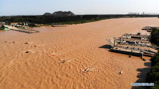 In this aerial photo, the floating bridge over the Yellow River at Luokou is temporarily dismantled as a flood is expected to soon reach Jinan, capital of east China's Shandong Province, on Sept. 18, 2019. (Xinhua/Wang Kai)
