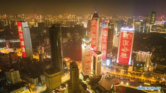 Aerial photo taken on Jan. 31, 2020 shows buildings illuminated with slogans to cheer the city on in Wuhan, central China's Hubei Province. (Xinhua/Xiao Yijiu)