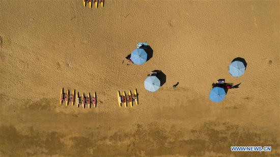 Aerial photo taken on Sept. 28, 2020 shows people enjoying themselves at the seaside of Rizhao City, east China's Shandong Province. China is set to welcome eight days of national holiday this year as the Mid-Autumn Festival coincide with the country's National Day. (Xinhua/Fan Changguo)