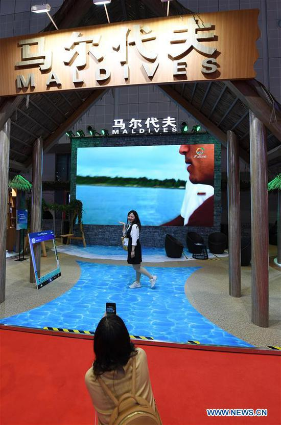 A visitor poses for photos at the Maldives pavilion during the second China International Import Expo (CIIE) in Shanghai, east China, Nov. 6, 2019. (Xinhua/Fan Peishen)
