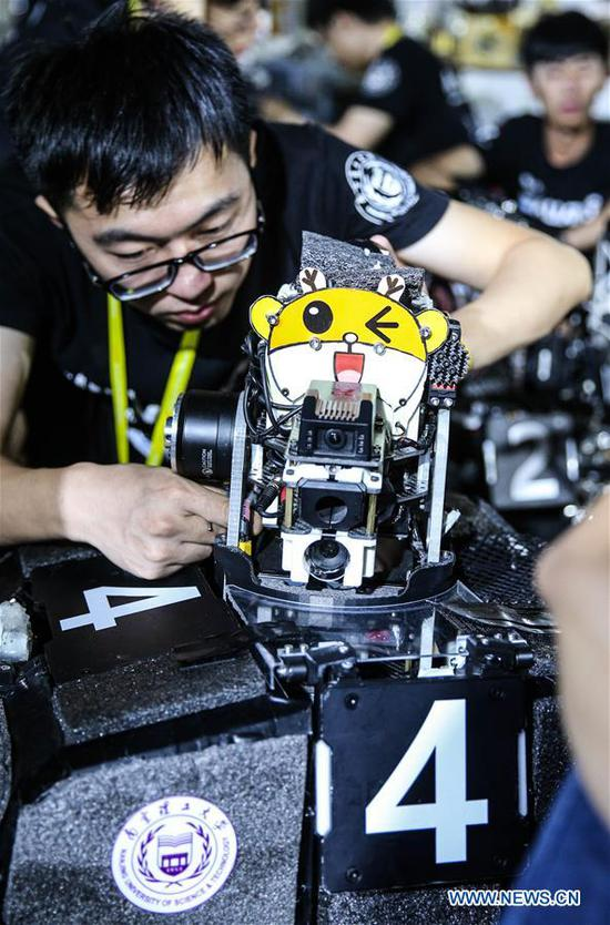 A participant tests a robot during the finals of the 18th RoboMaster Robotics Competition in Shenzhen, south China's Guangdong Province, Aug. 6, 2019. The final tournament of the 18th RoboMaster Robotics Competition kicked off here on Tuesday, with 32 teams from home and abroad competing for the championship. (Xinhua/Jin Yu)