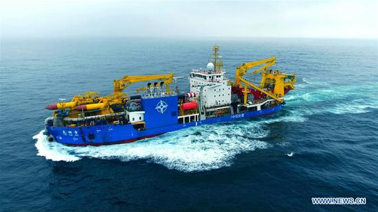 Tian Kun Hao, a Chinese-built dredging vessel, the largest of its kind in Asia, sails under a sea trial after departing a port in east China's Jiangsu Province, June 12, 2018. Tian Kun Hao, constructed by Tianjin Dredging Co. Ltd., a subsidiary of China Communication Construction Co., Ltd. (CCCC), finished its first sea trial. The 140-meter-long vessel, with the designed capacity to dredge 6,000 cubic meters per hour, can dig as deep as 35 meters under the sea floor. (Xinhua/Mao Zhenhua)