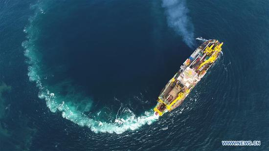 Tian Kun Hao, a Chinese-built dredging vessel, the largest of its kind in Asia, sails under a sea trial after departing a port in east China's Jiangsu Province, June 11, 2018. Tian Kun Hao, constructed by Tianjin Dredging Co. Ltd., a subsidiary of China Communication Construction Co., Ltd. (CCCC), finished its first sea trial. The 140-meter-long vessel, with the designed capacity to dredge 6,000 cubic meters per hour, can dig as deep as 35 meters under the sea floor. (Xinhua/Mao Zhenhua)