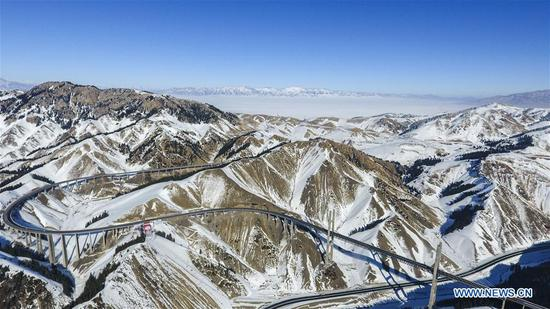 Aerial photo taken on Jan. 26, 2018 shows the Lianyungang-Horgos expressway along the Tianshan Mountains, northwest China's Xinjiang Uygur Autonomous Region. As an important link of the Silk Road Economic Belt, Xinjiang is speeding up the development of transportation and logistics to connect east and west. By the end of 2017, the total length of roads in Xinjiang reached 186,000 km, with 4,578 km of expressways. (Xinhua/Hu Huhu)