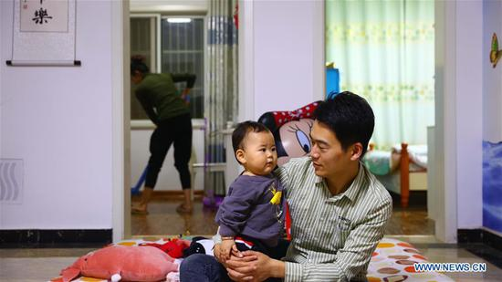 Wu Wenguang (R), 26, stays with his daughter after returning home from a day's work in Guzhen County of Bengbu, east China's Anhui Province, Oct. 6, 2018. (Xinhua/Qu Yan)