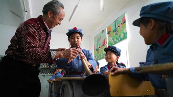 Xiao Qinghua (1st L) teaches a student to play the suona horn at the Changzhengyuan primary school in Yudu County, east China's Jiangxi Province, on Oct. 11, 2018. Xiao, an inheritor of the national intangible cultural heritage