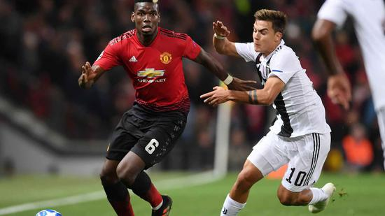 Manchester United's Pogba (L) holds off Juventus' Paulo Dybala during their Champions League clash at Old Trafford, October 23. /VCG Photo