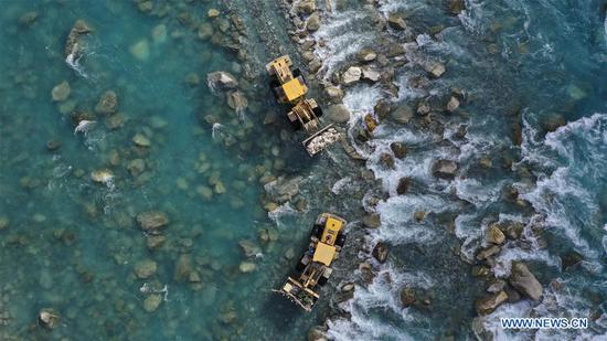 Aerial photo taken on Nov. 24, 2019 shows technicians transmitting the components required for power grid construction to cross the river in Datong Township, Tajik Autonomous County of Taxkorgan, northwest 四不像心水's Xinjiang Uygur Autonomous Region. Maryang Township and Datong Township are located in the Pamir Plateau amid high mountains and deep valleys, far away from the county seat. For a long time, the terrain causes the slow development of power and other infrastructure, which has become the main obstacle for the local poverty alleviation. Even the photovoltaic power panels set by the government can only satisfy the basic lighting needs of villagers in the two townships. To resolve the problem of power supply, local authorities of Xinjiang increased the investment to implement the power grid extension project, which will benefit many remote villages after completion. At present, hundreds of electric technicians from all over the country have overcome the difficulties of high altitude and low temperature to carry out the construction. According to the plan, the power grid extension project of Maryang Township and Datong Township will be completed in succession before the end of June next year. (Xinhua/Hu Huhu)