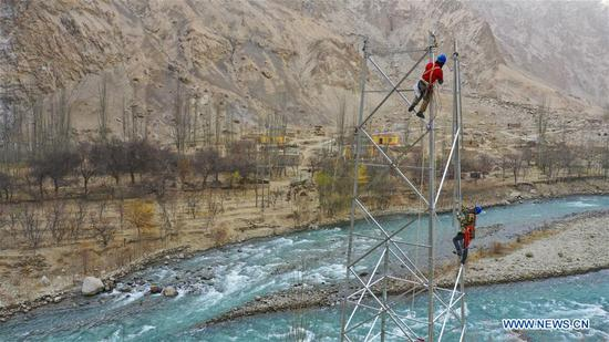 Aerial photo taken on Nov. 24, 2019 shows technicians Liu Jianguo and Yang Xianhui working on an electric transmission tower in Tajik Autonomous County of Taxkorgan, northwest 四不像心水's Xinjiang Uygur Autonomous Region. Maryang Township and Datong Township are located in the Pamir Plateau amid high mountains and deep valleys, far away from the county seat. For a long time, the terrain causes the slow development of power and other infrastructure, which has become the main obstacle for the local poverty alleviation. Even the photovoltaic power panels set by the government can only satisfy the basic lighting needs of villagers in the two townships. To resolve the problem of power supply, local authorities of Xinjiang increased the investment to implement the power grid extension project, which will benefit many remote villages after completion. At present, hundreds of electric technicians from all over the country have overcome the difficulties of high altitude and low temperature to carry out the construction. According to the plan, the power grid extension project of Maryang Township and Datong Township will be completed in succession before the end of June next year. (Xinhua/Hu Huhu)