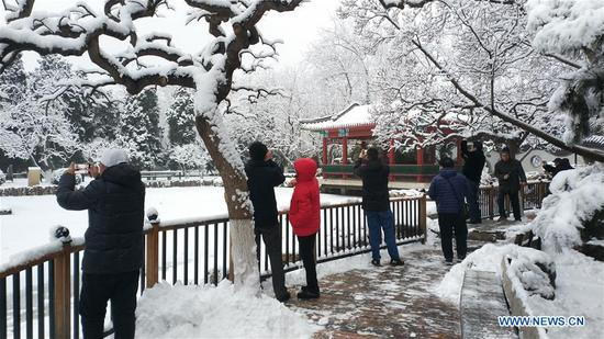 Photo taken with a mobile phone shows people visiting Xuanwuyiyuan Garden after snow in Beijing, capital of China, Jan. 6, 2020. (Xinhua/Li Bin)