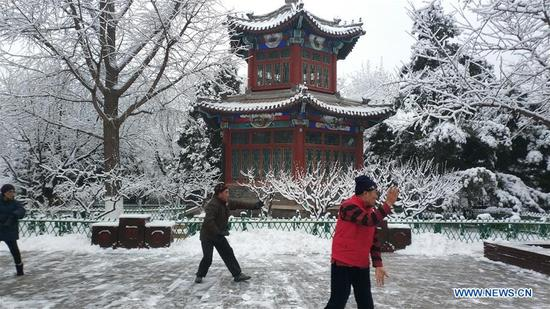 Photo taken with a mobile phone shows people exercising at Xuanwuyiyuan Garden after snow in Beijing, capital of China, Jan. 6, 2020. (Xinhua/Li Bin)