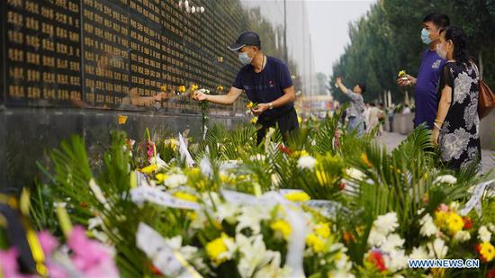 People mourn for the deceased in the 1976 Tangshan Earthquake in front of a memorial wall in Tangshan, north China's Hebei Province, July 28, 2020, the 44th anniversary of the earthquake. (Photo by Dong Jun/Xinhua)