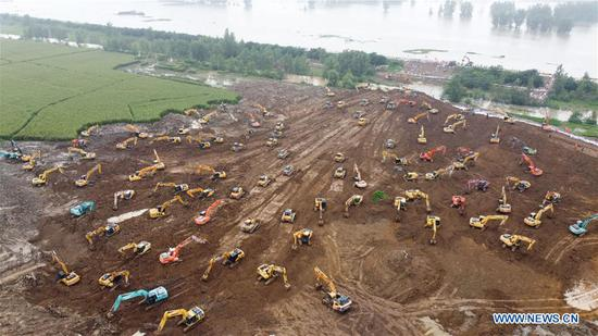 Aerial photo taken on July 28, 2020 shows heavy machineries working to build a temporary embankment to prevent possible flood water from a broken sluice gate on the embankment of Daijia Lake in a flood storage area in Yingshang County, east China's Anhui Province. A large number of heavy machineries have been deployed here to build a 600-meter-long temporary embankment on land side of the Daijia Lake embankment to prevent flood water if the embankment sluice gate were broken. (Xinhua/Zhang Duan)