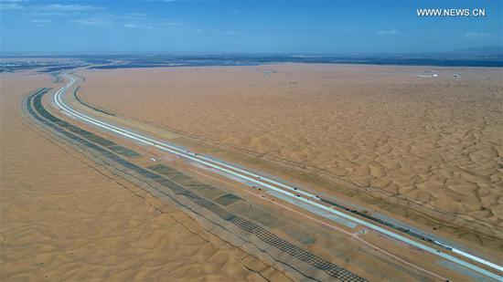 Aerial photo taken on Sept. 7, 2020 shows the construction site of the Qingtongxia-Zhongwei section of the Wuhai-Maqin highway in northwest China's Ningxia Hui Autonomous Region. The Qingtongxia-Zhongwei section of the Wuhai-Maqin highway is under construction, of which an 18-kilometer-long section going through the Tengger Desert is the first desert highway in Ningxia. A desertification control team has worked along the highway construction site, using straw checkerboard barriers and planting vegetation to stop the dunes from moving or expanding. (Xinhua/Wang Peng)