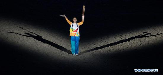 A schoolgirl holds the Queen's Baton during the opening ceremony of the 2018 Gold Coast Commonwealth Games at the Carrara Stadium in the Gold Coast, Australia, April 4, 2018. (Xinhua/Zhu Hongye)