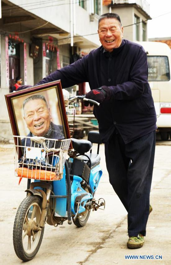 A villager goes home with his photo in Xiawei Village of Youlan Town, Nanchang City, east China's Jiangxi Province, Nov. 22, 2020. Since 2014, volunteers from a non-profit organization in Nanchang City have kept on taking photos of smiling faces of farmers aged over 70 years old in nearby villages. The portait photos taken by volunteers were given to farmers for free. By far, the volunteers have taken nearly 4,350 people and 50,000 photos. They aim at collecting high-definition images of 10,000 farmers within 10 years. (Xinhua/Chen Chunyuan)