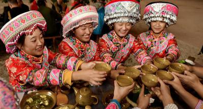 Miao people enjoy food during long-table banquet in SW China's Sichuan