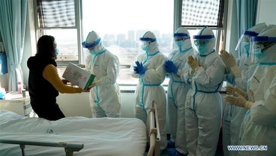 Ms Yan receives a birthday gift from medical workers when leaving hospital after recovery from novel coronavirus pneumonia (NCP) at a hospital in Wuhan, central China's Hubei Province, Feb. 18, 2020. On the day of her birthday, Yan was discharged from hospital after recovery. (Xinhua/Wang Yuguo)