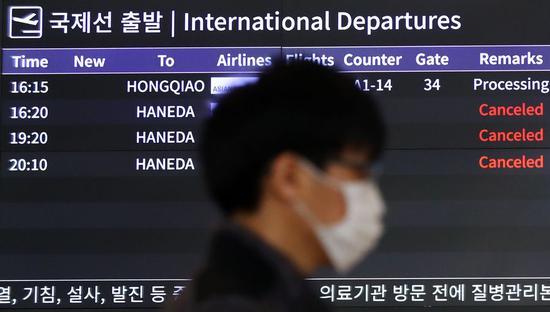 A screen shows that some flights to Tokyo are cancelled at Gimpo International Airport in Seoul, South Korea, March 9, 2020.(NEWSIS/Handout via Xinhua)